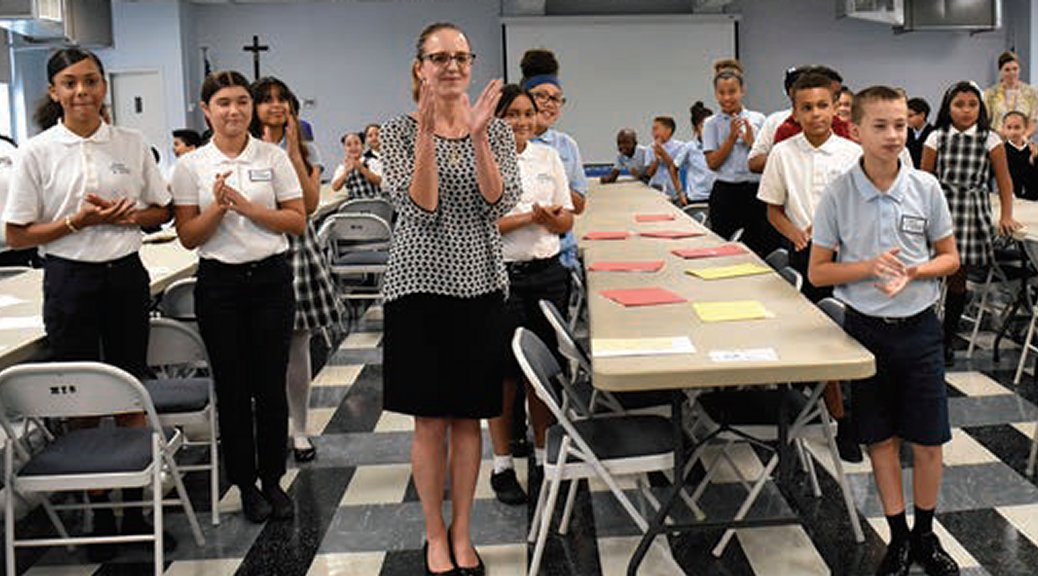 Students welcome Fransiscan Sister Virginelle and Monsignor Robert Kozal to the school cafeteria.